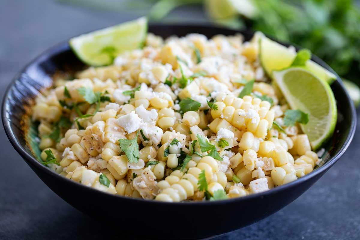 bowl of Mexican Corn Salad with limes and cilantro