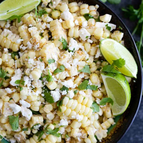 overhead view of grilled corn salad with cheese, cilantro and limes
