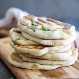 a stack of naan bread on a cutting board sprinkled with cilantro