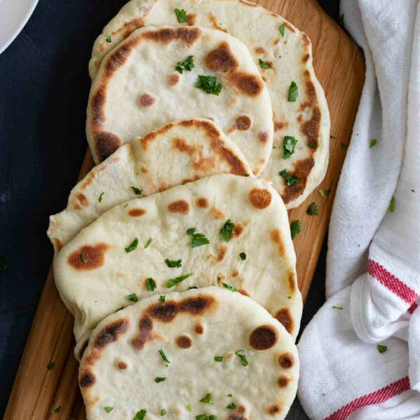 overhead view of naan bread on a cutting board with a white towel