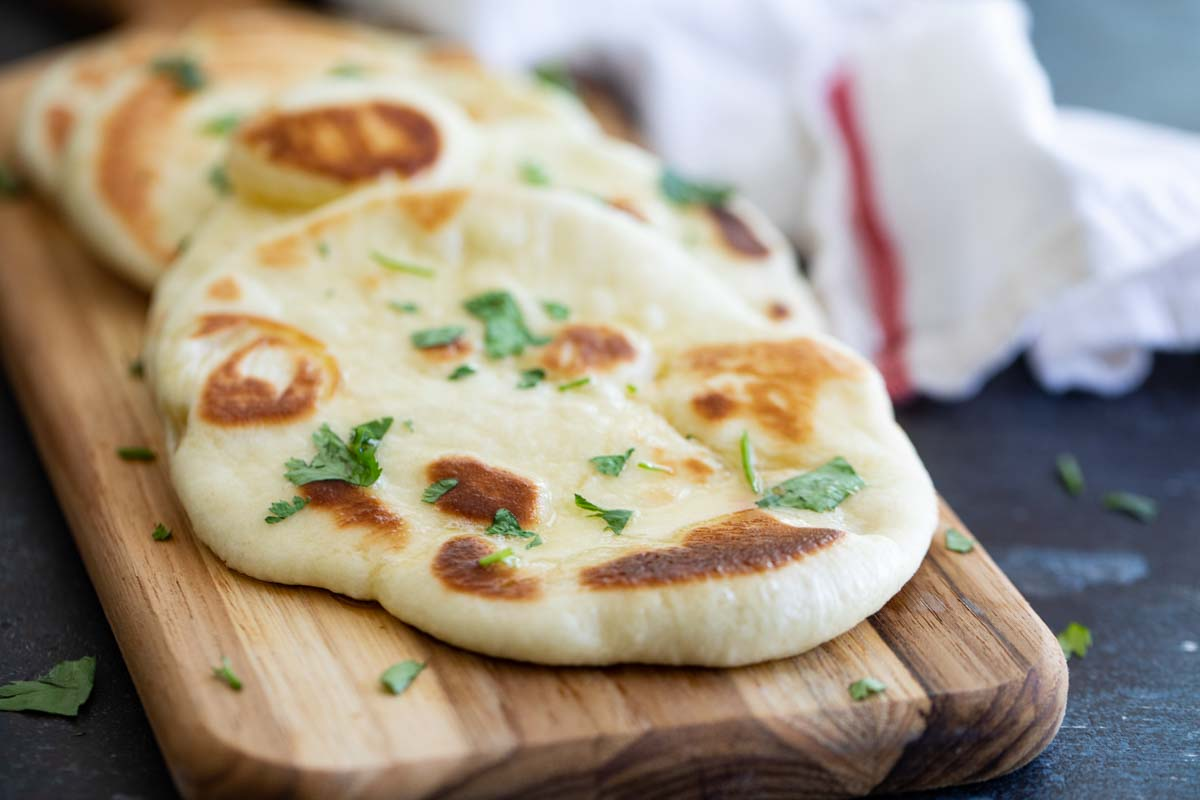 homemade naan bread sprinkled with cilantro on a cutting board