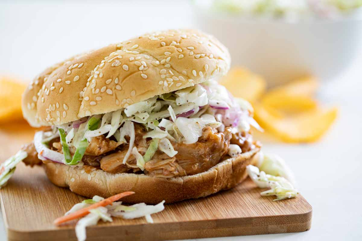 Teriyaki Chicken Sandwich topped with coleslaw on a cutting board