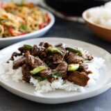 Mongolian Beef over rice on a white plate