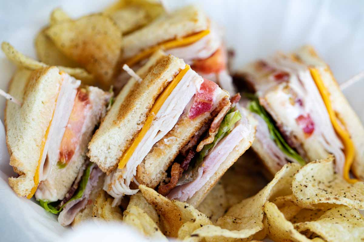 pieces of club sandwich in a basket with potato chips