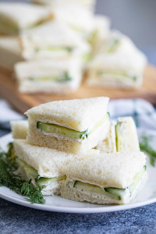 cucumber sandwiches stacked on a white plate