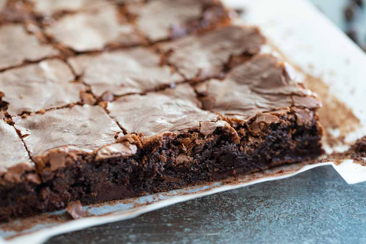 homemade brownies on parchment paper cut into squares