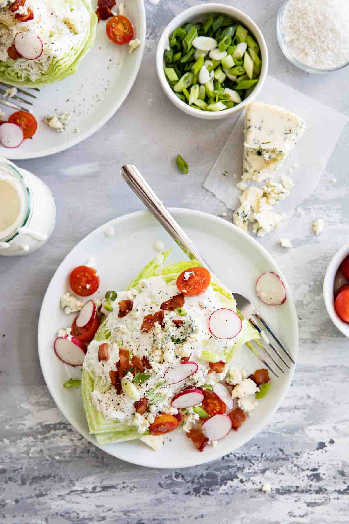 overhead view of wedge salad on plates with blue cheese and green onions