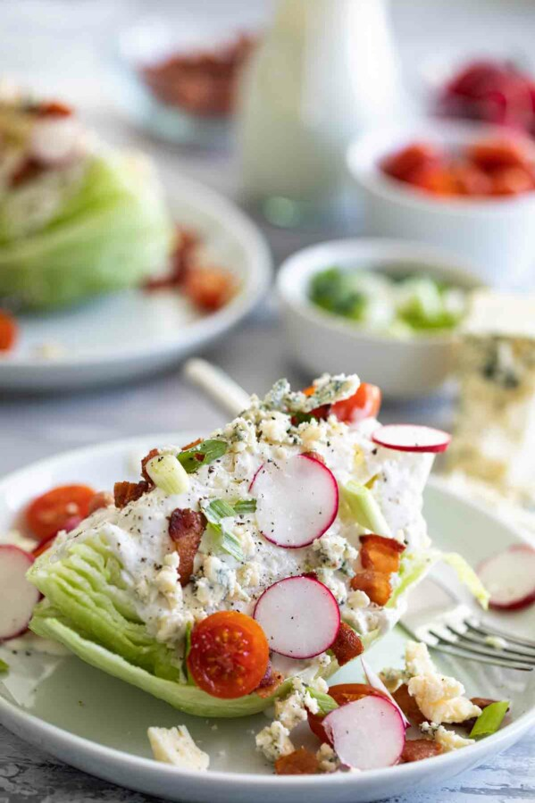 wedge salad on a plate with tomatoes, radishes and bacon