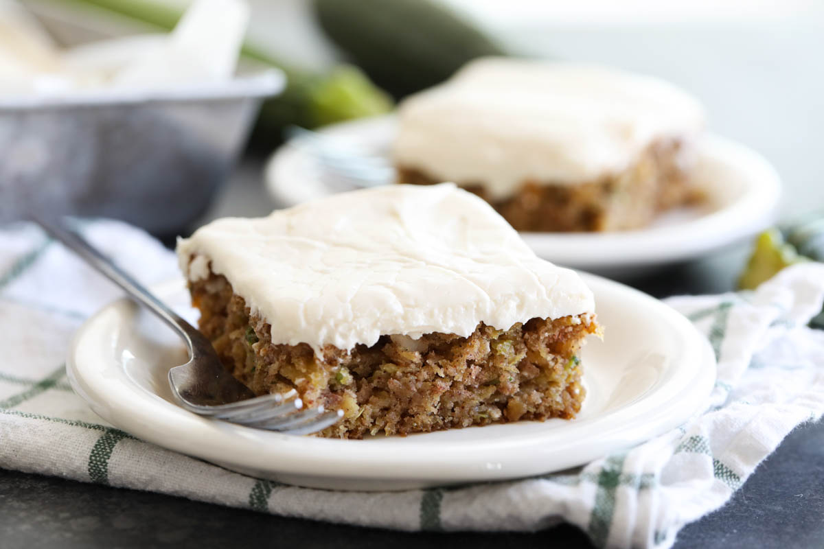 slice of zucchini cake on a plate with another plate behind it