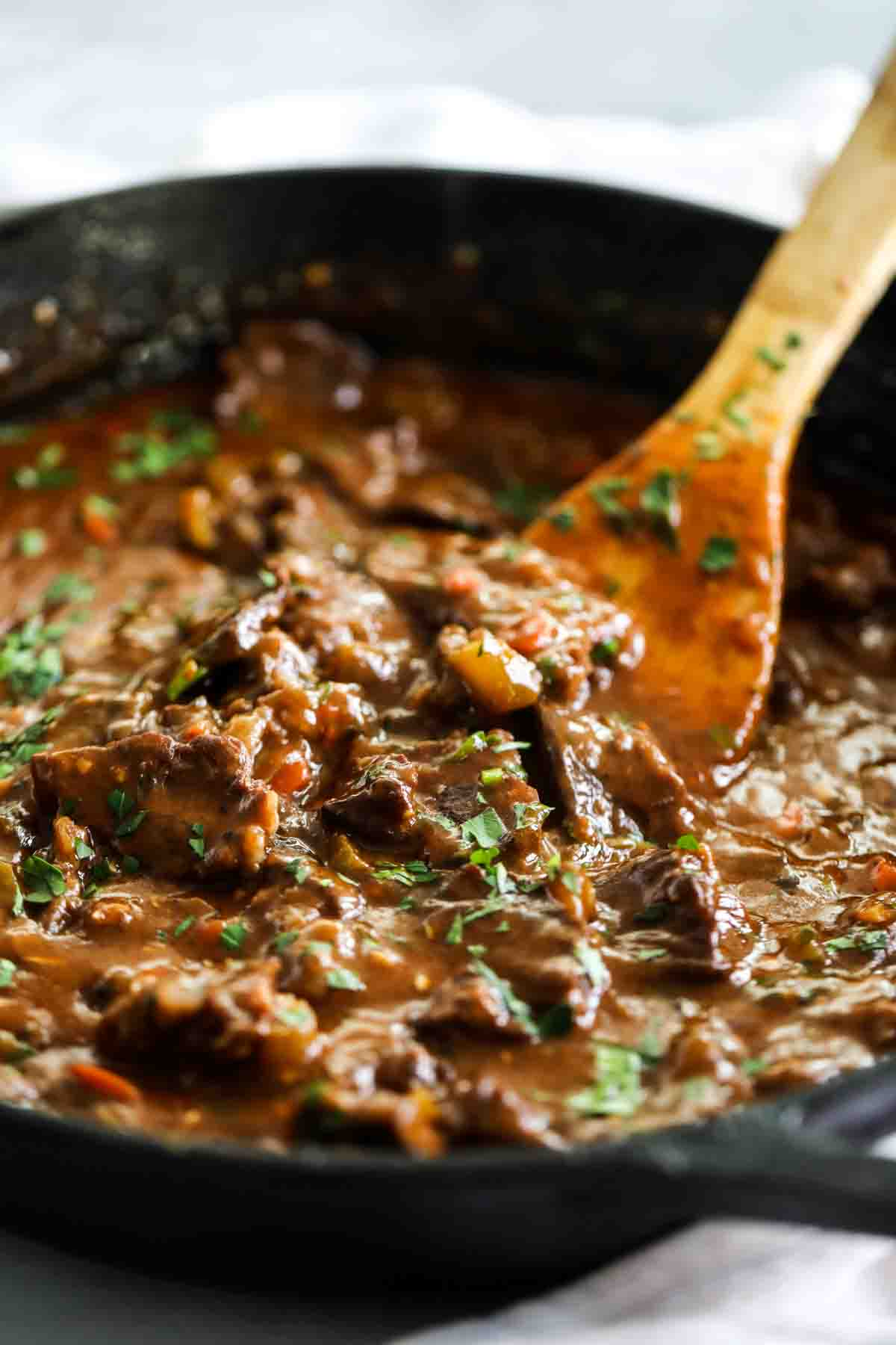 beef tips and gravy in a skillet with a wooden spoon