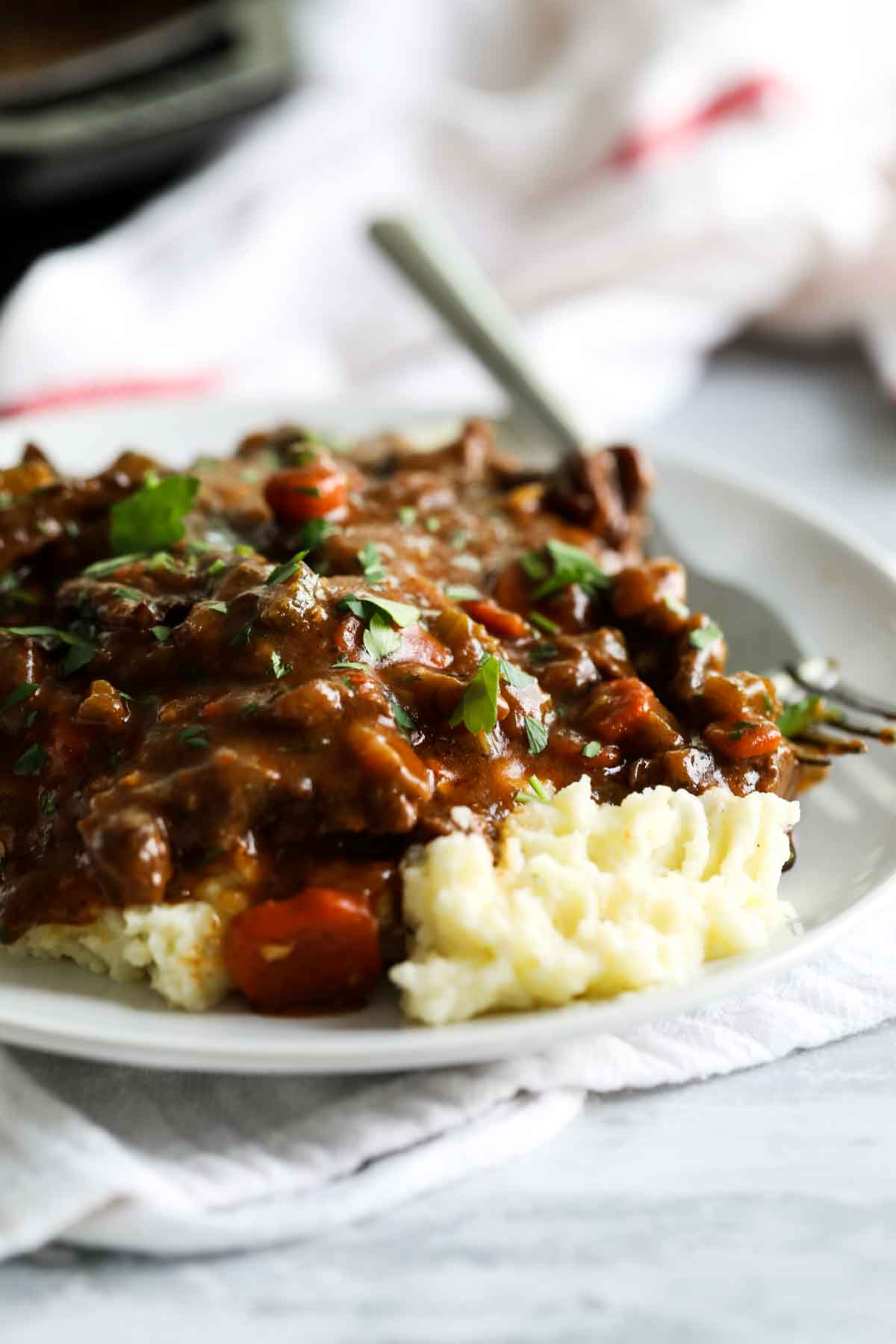 beef tips and gravy over mashed potatoes on a plate