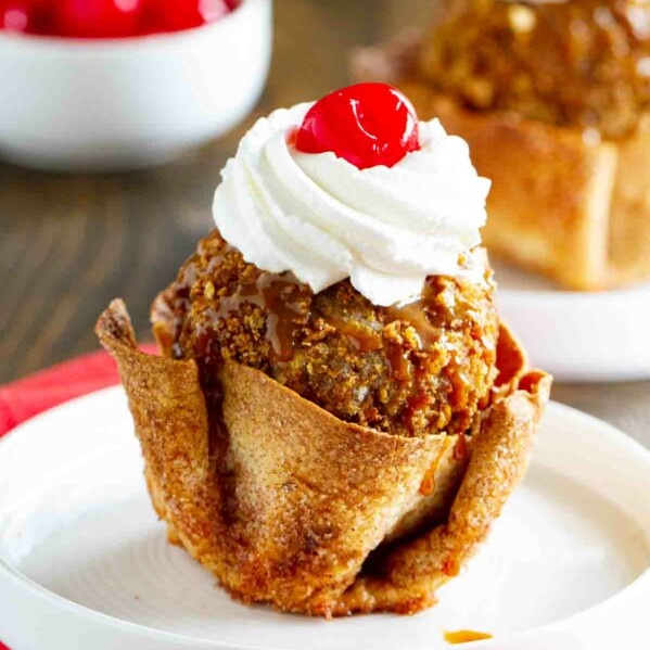 fried ice cream in a tortilla bowl sitting on a white plate