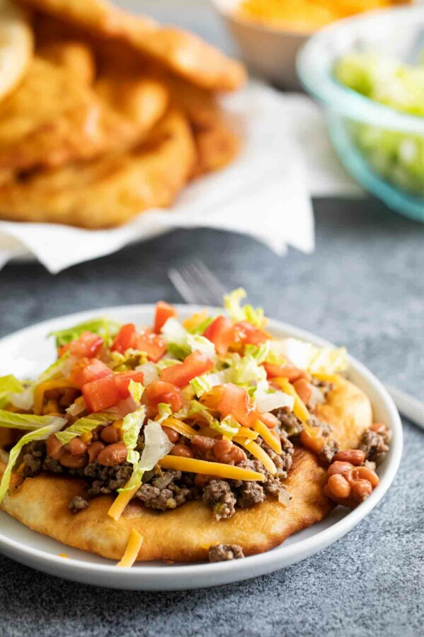 Navajo taco topped with meat and beans with fry bread in the background