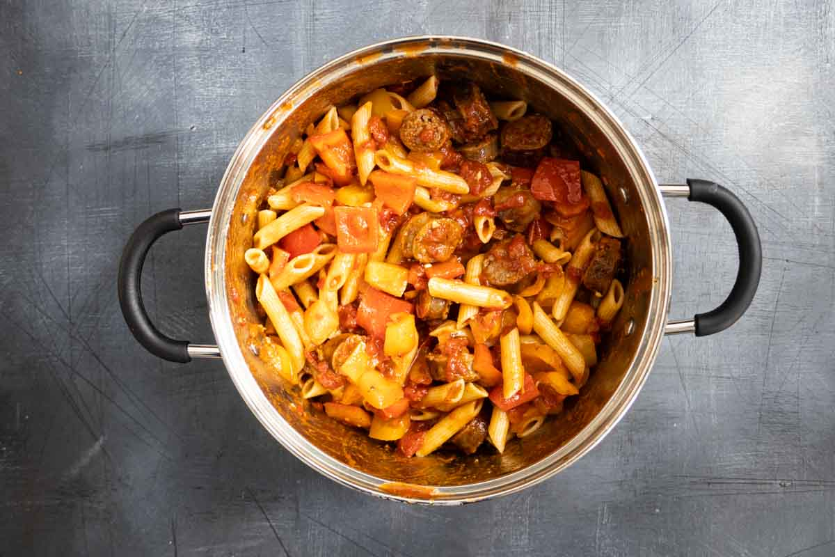 pot filled with pasta, peppers and sausage with sauce
