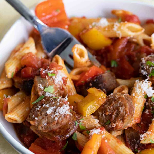 bowl of sausage and peppers pasta with a fork