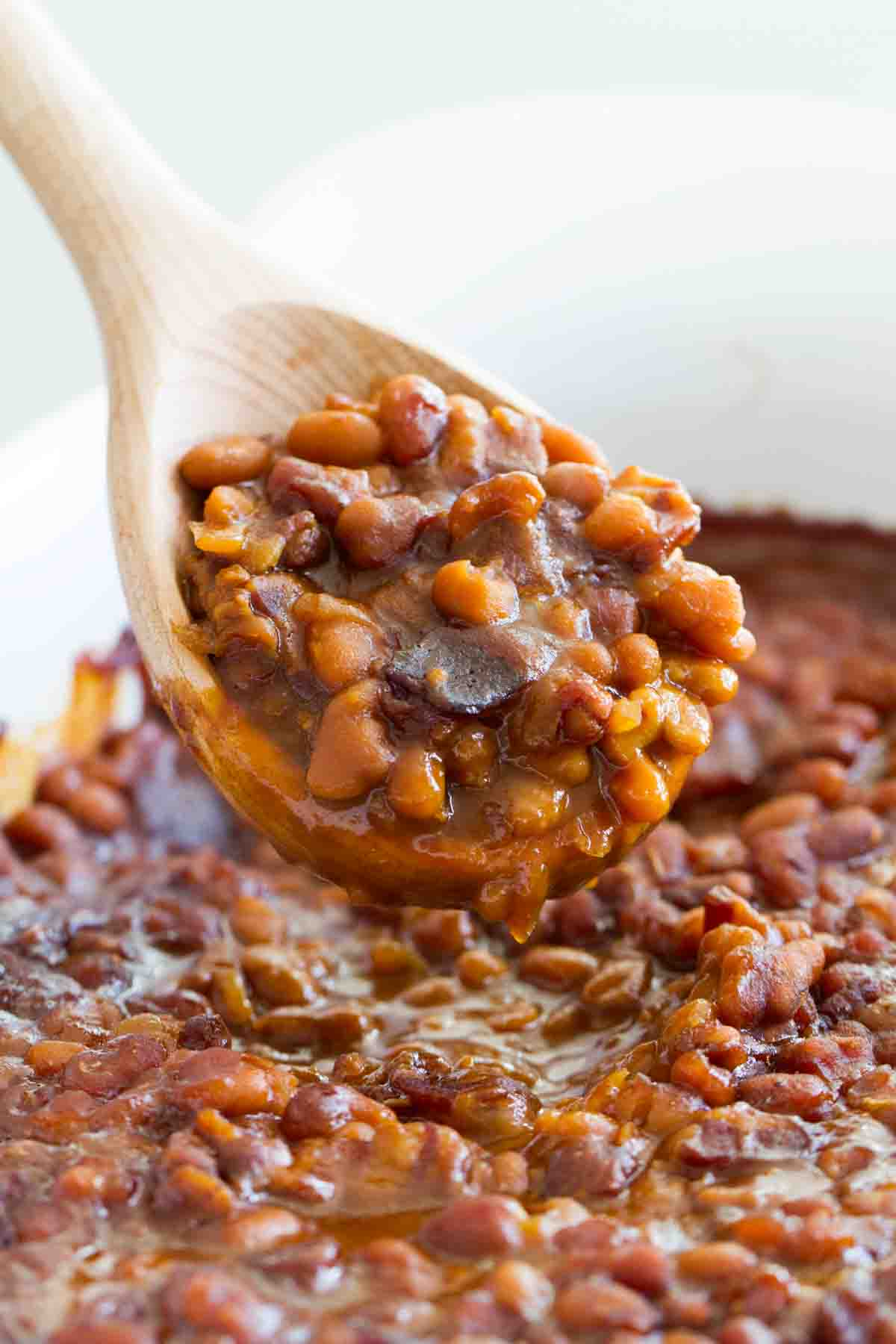 scoop of baked beans with a wooden spoon