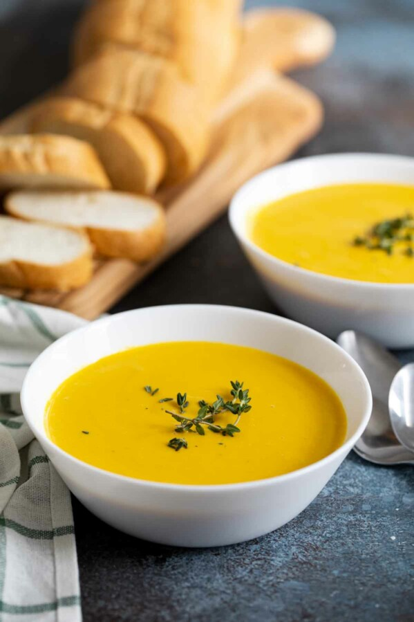 bowls of butternut squash soup with bread in the background