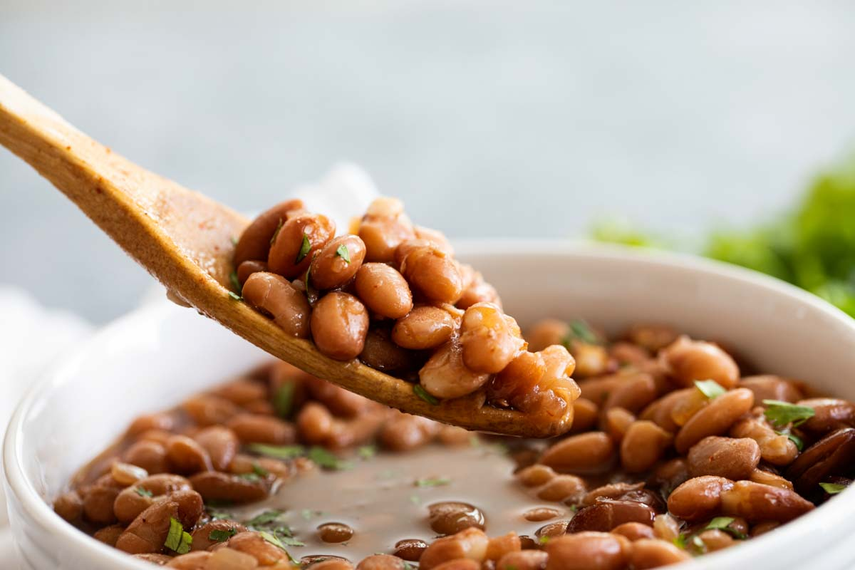 spoonful of beans with a wooden spoon