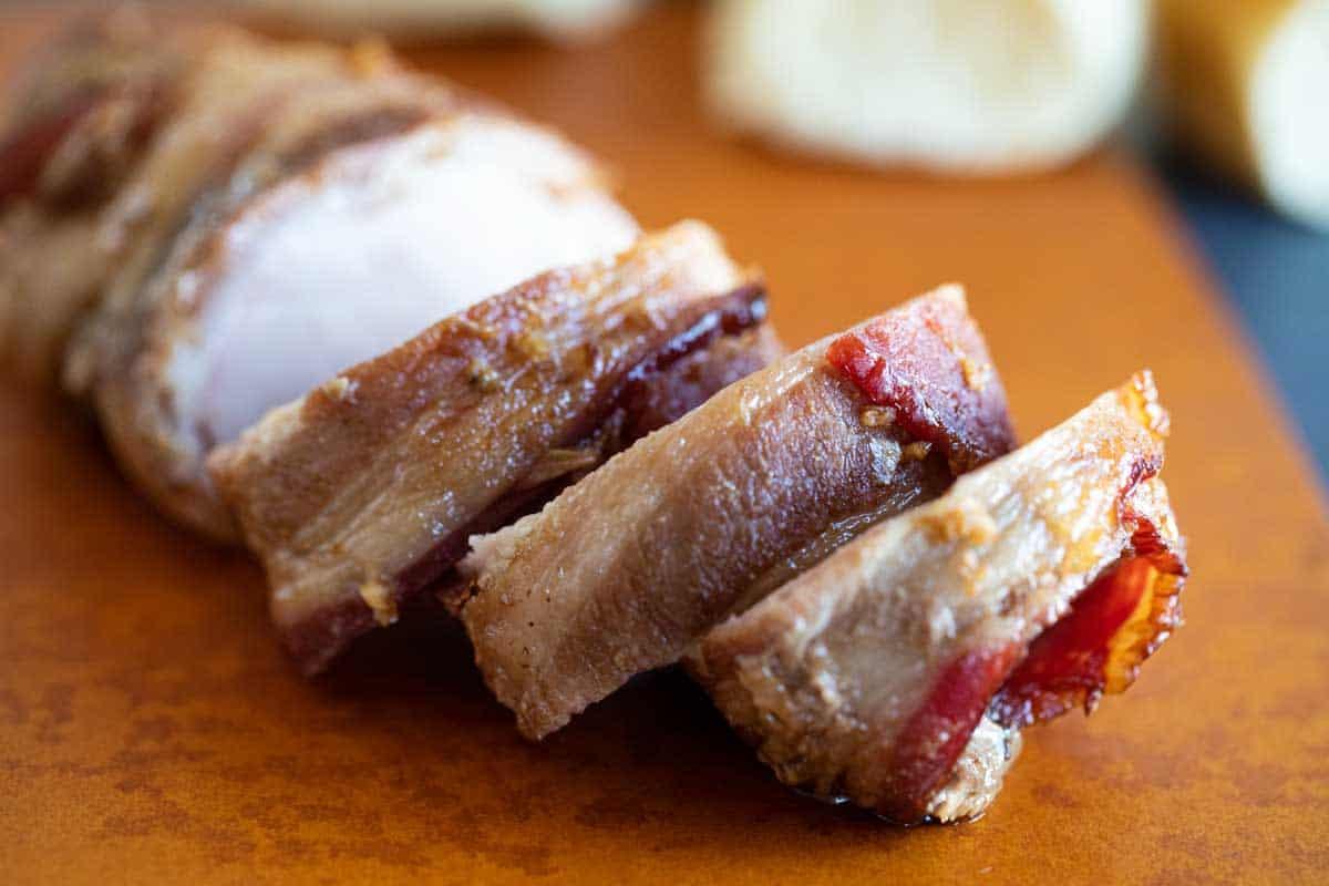 sliced bacon wrapped pork tenderloin on a cutting board