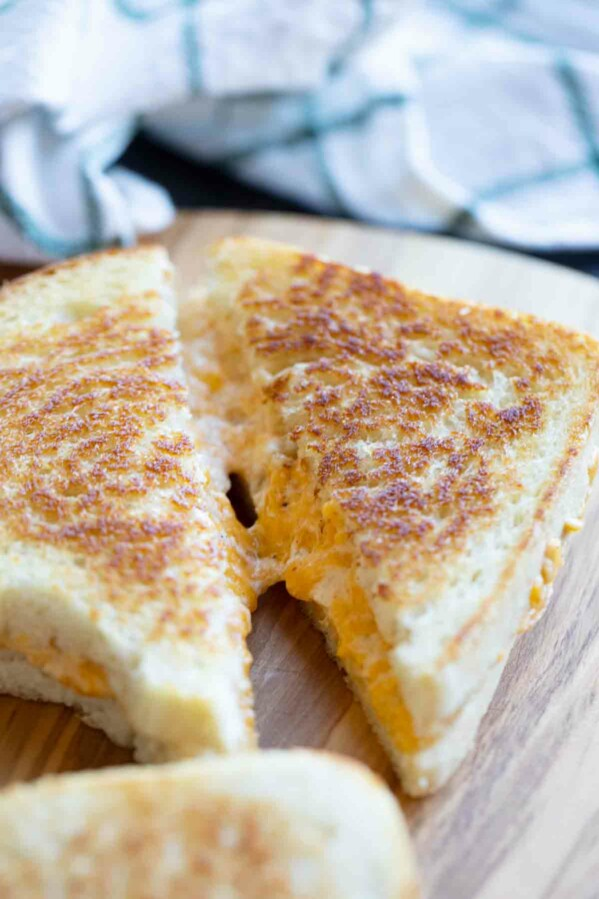 sliced grilled cheese sandwich showing gooey cheese